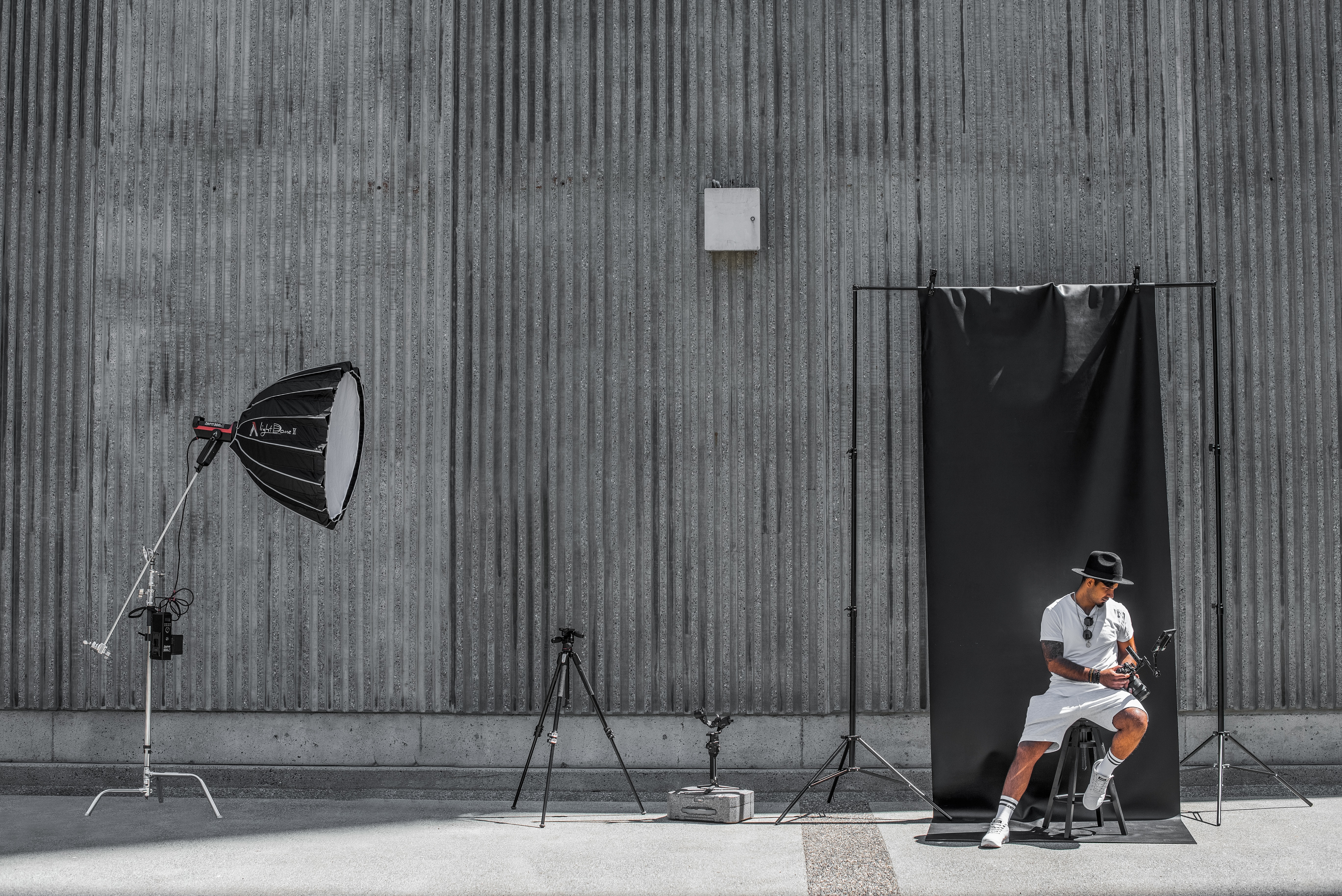 A professional male model on a shoot against a metal wall