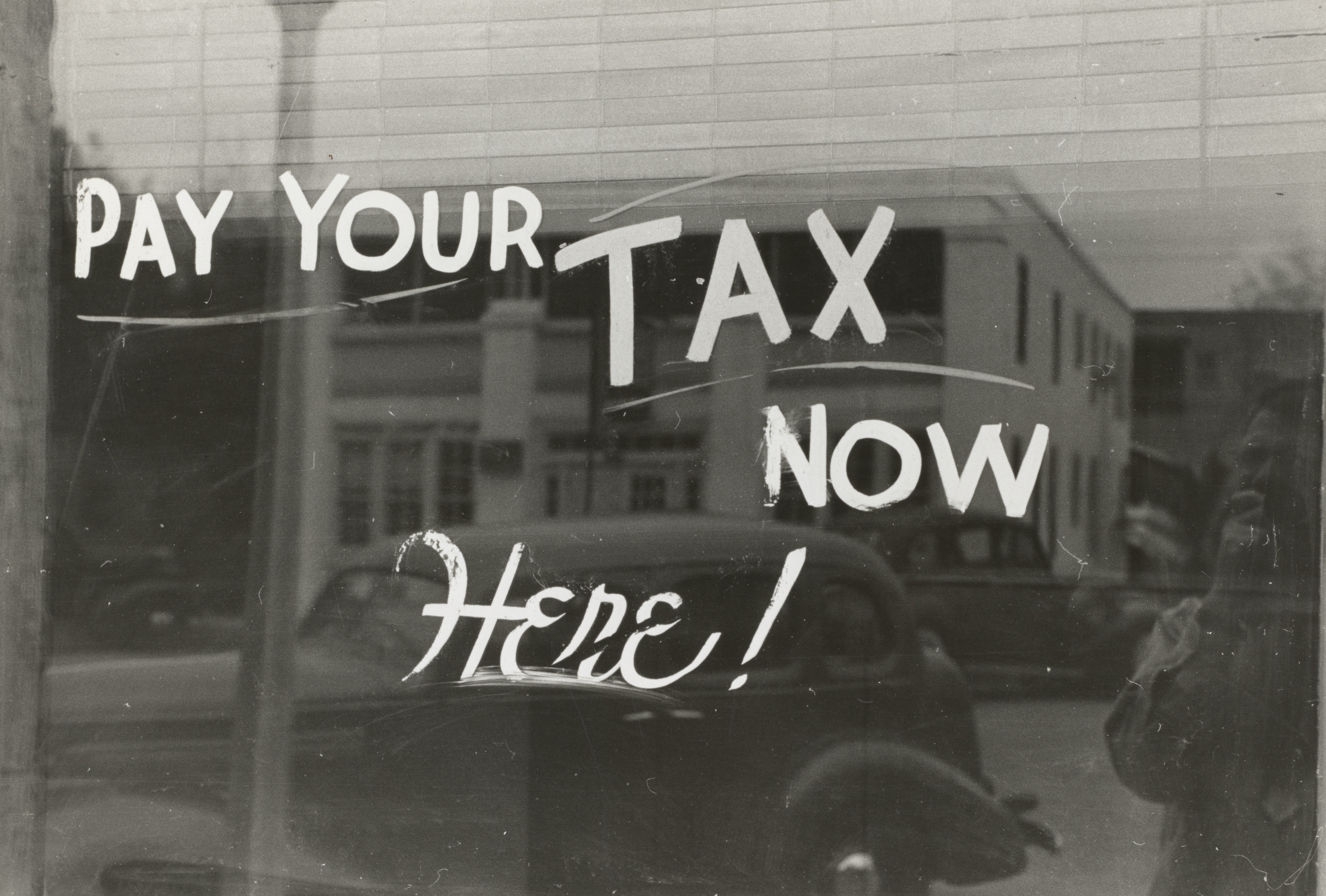 """A Window with writing on saying """"Pay Your Tax Now Here"""""""